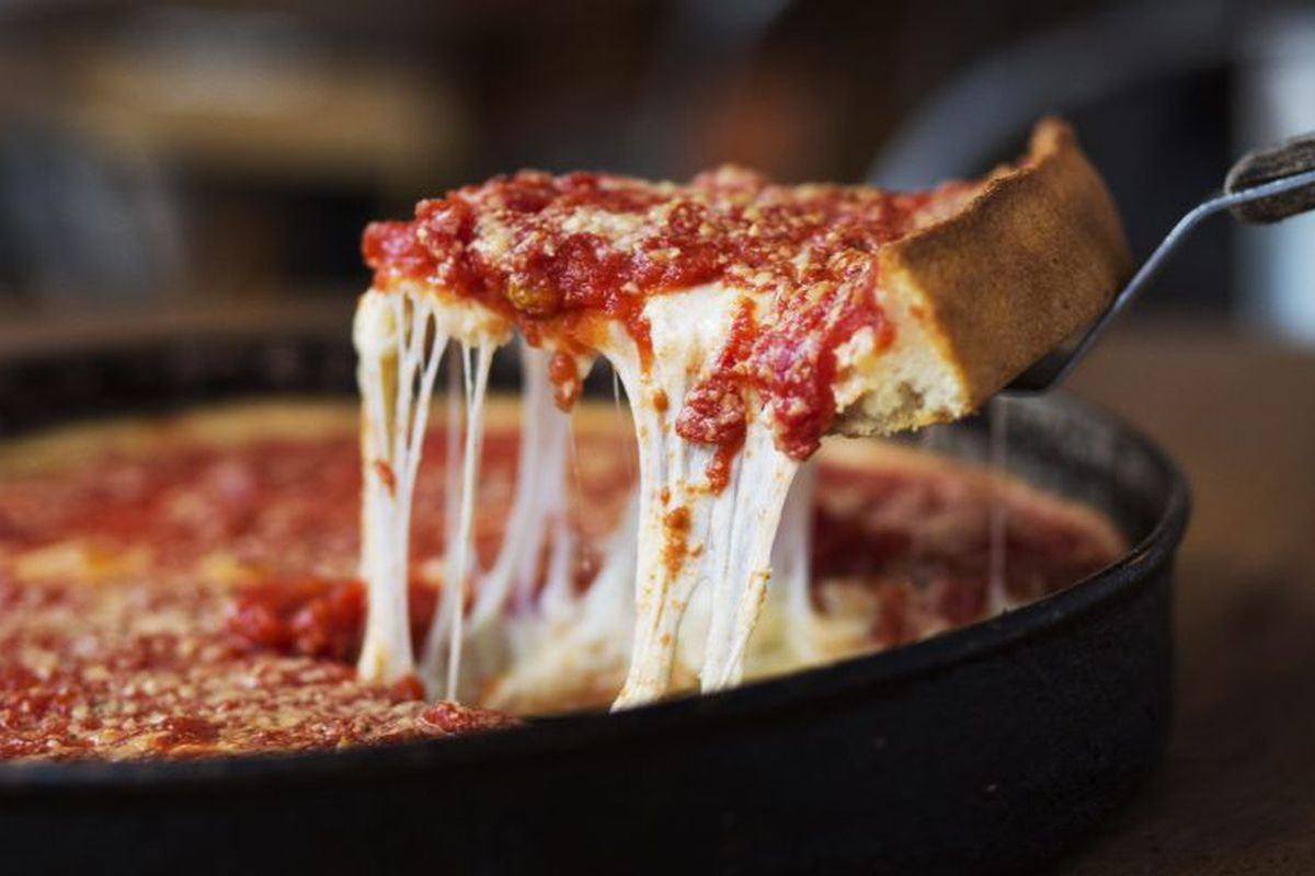 A slice of deep dish pizza is pulled from the pie.