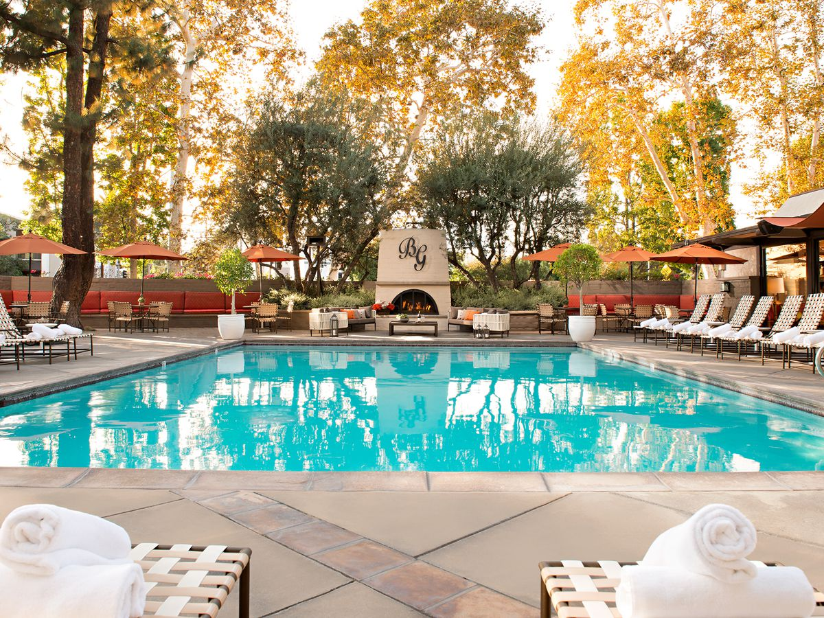 An autumn day showing a shaded pool surrounded by lounge chairs.