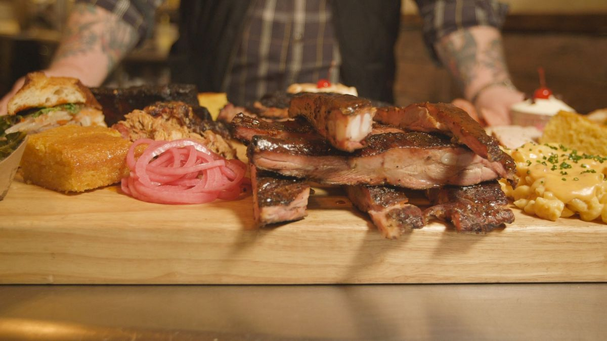 A spread of barbecued meat and sides on a butcher's block at Hometown