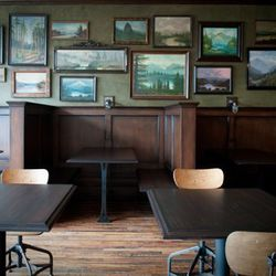 Emblematic of the new Portland aesthetic — reclaimed dark wood, hanging Edison bulbs, and industrial-looking furniture — the Woodsman Tavern's dining room simultaneously looks modern and vintage, encapsulating the de rigeuer design trend in one glowing, i