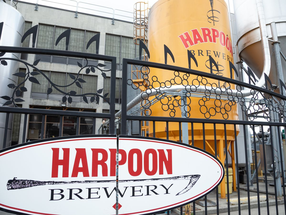 """The front of a brewery, with a long cylindrical tower with """"Harpoon"""" painted on it."""