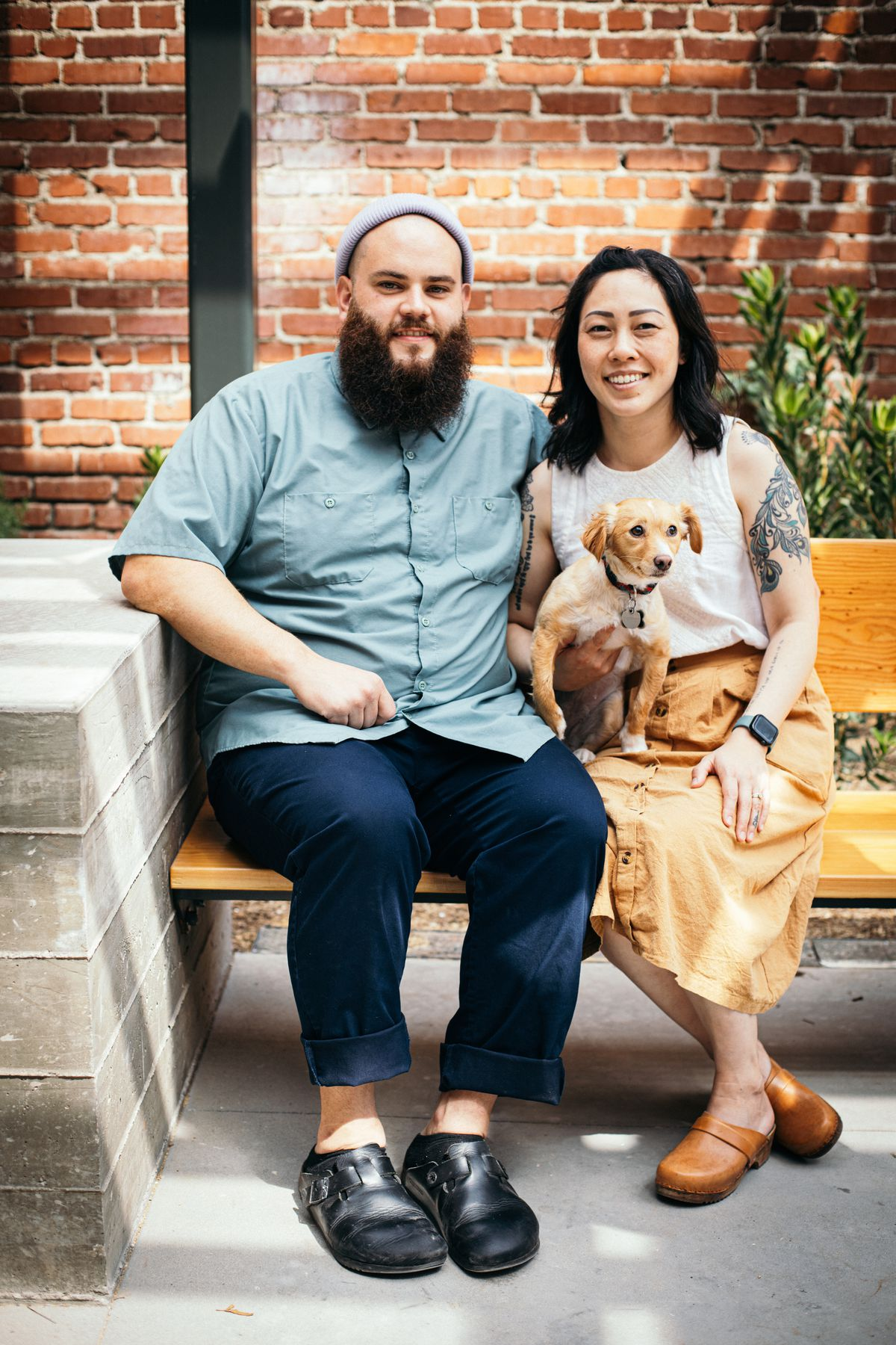 A pair of chefs hold a dog while sitting in front of a brick wall at their restaurant.