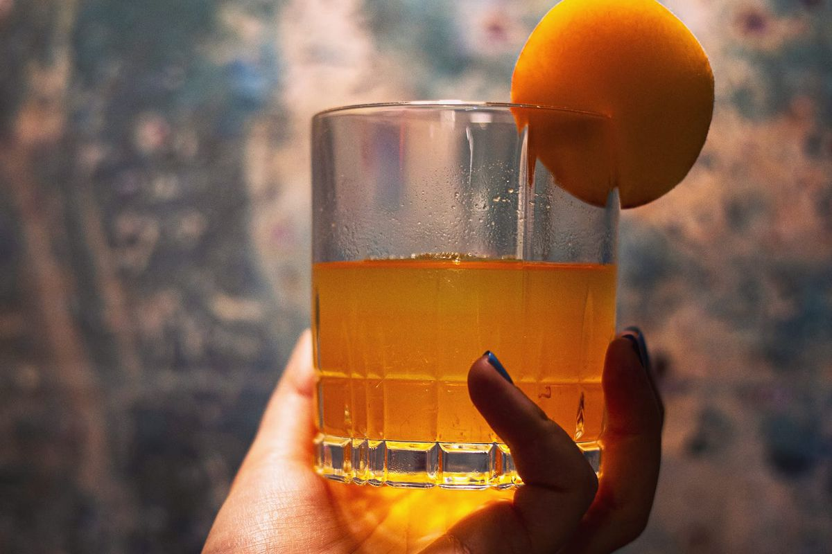 A hand holding up an orange cocktail with a slide of orange fruit on the rim