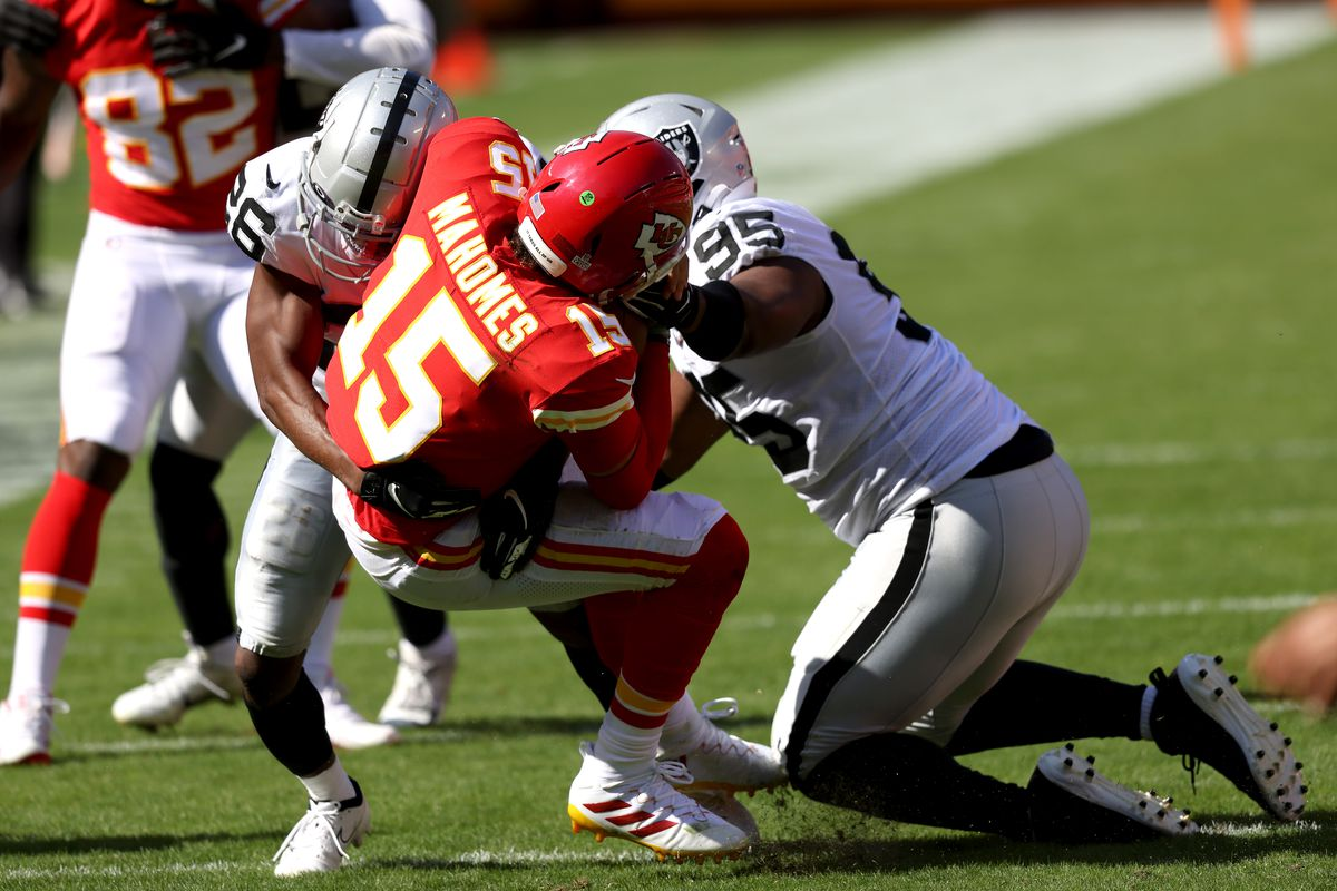 Patrick Mahomes #15 of the Kansas City Chiefs is wrapped up by Datone Jones #95 and Nevin Lawson #26 of the Las Vegas Raiders during the third quarter at Arrowhead Stadium on October 11, 2020 in Kansas City, Missouri.