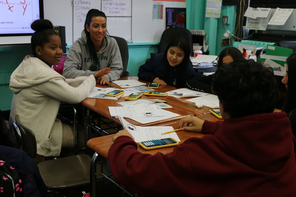 An eighth-grade math teacher discusses a problem with students at I.S. 96 and encourages a student who is learning English as a new language to explain his answer. Roughly half of his peers are also learning the language.