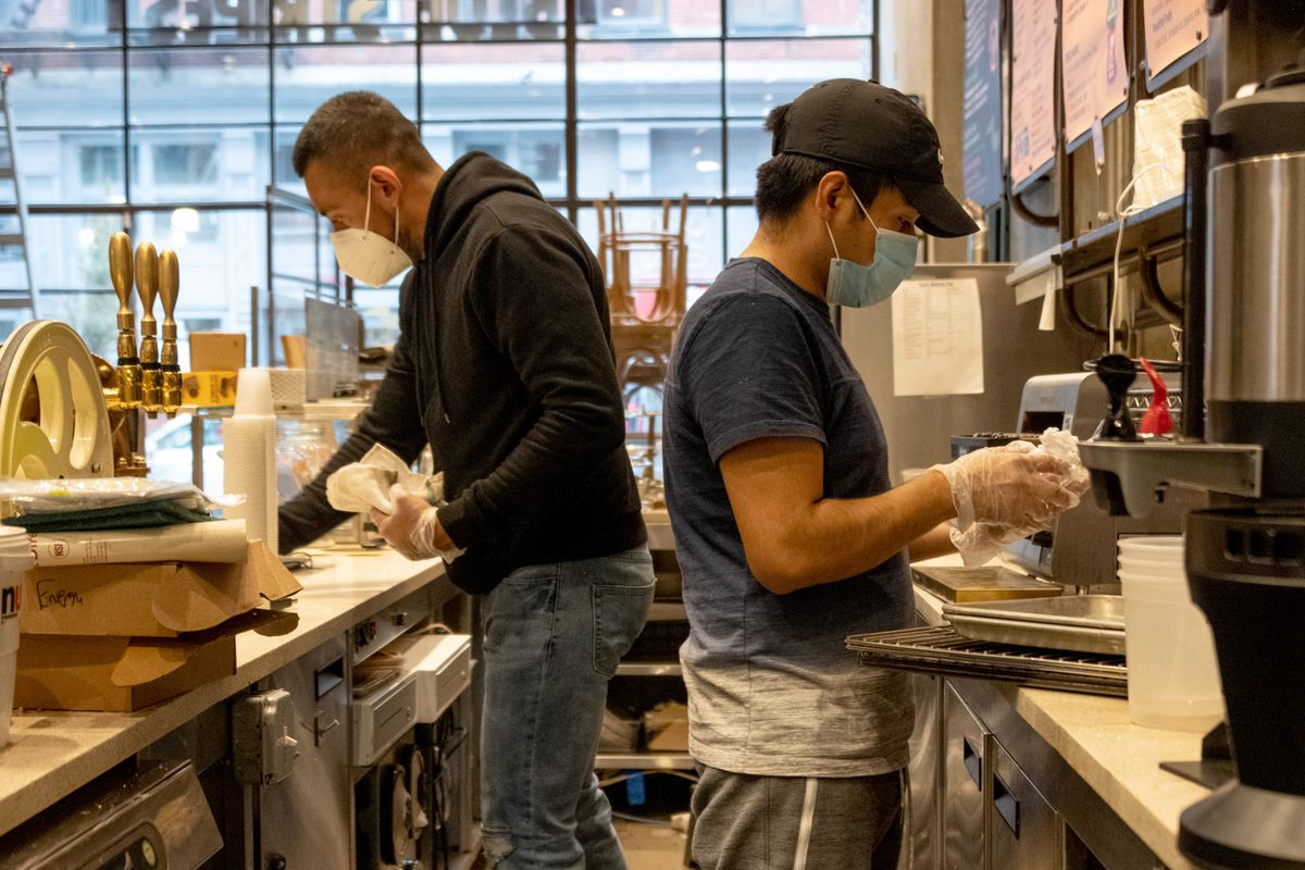 Two men wearing masks clean behind the counter of a coffee shop.
