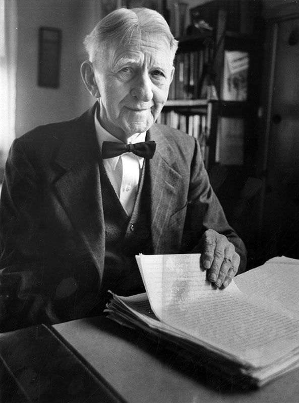 Black and white portrait of a old man with a large nose wearing a bowtie and holding papers.