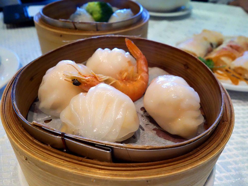 A view of steamed shrimp dumplings in a wooden serving vessel.