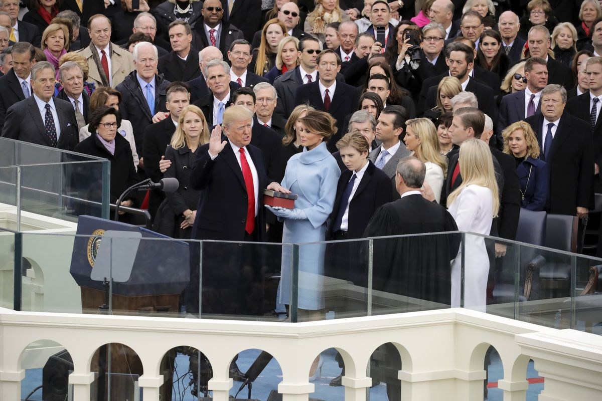 Supreme Court Justice John Roberts administers the oath of office to US President Donald Trump as his wife Melania Trump holds the Bible.