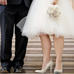 The bride wears a dress from LightInTheBox and Betsy Johnson shoes. The groom wears a Calvin Klein suit.