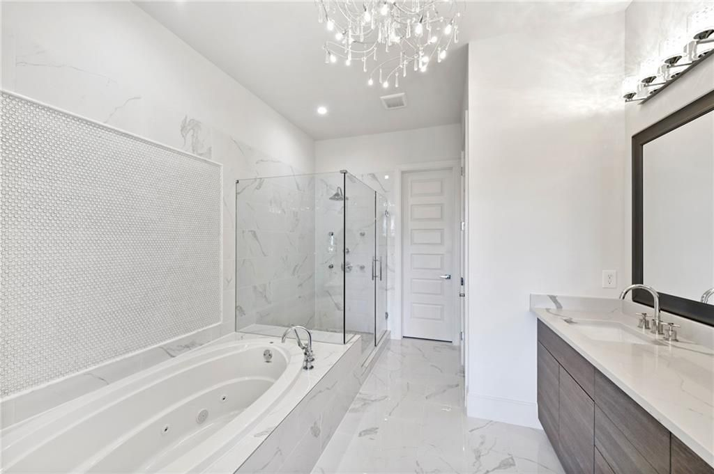 A white master bathroom with a large tub and two sinks.