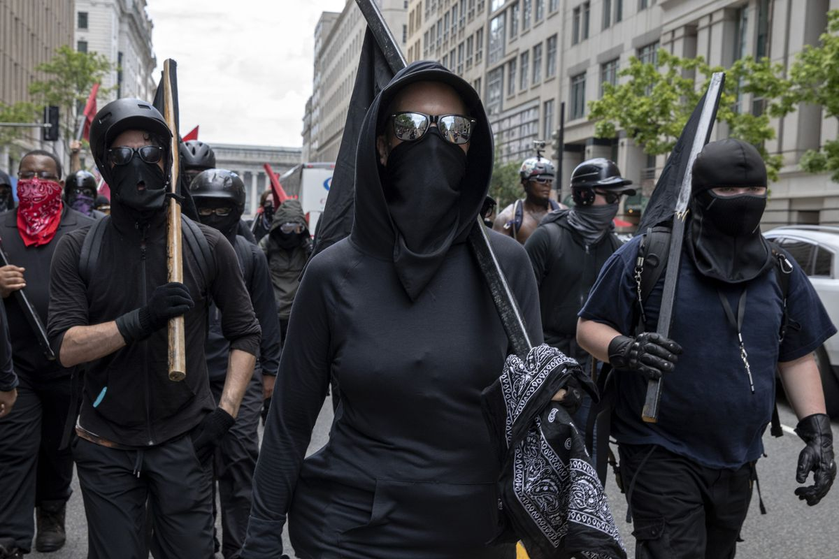A black-clad figure wearing sunglass and a black bandana over their mouth leads a crowd of more than ten similarly attired people down a DC street.