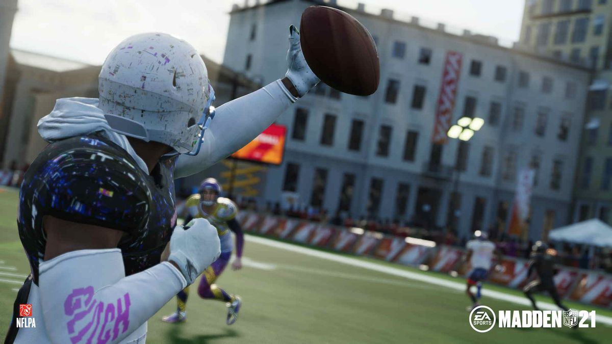 A player in a hoodie and a paint-spattered helmet prepares to punch a football, volleyball style, to a teammate.