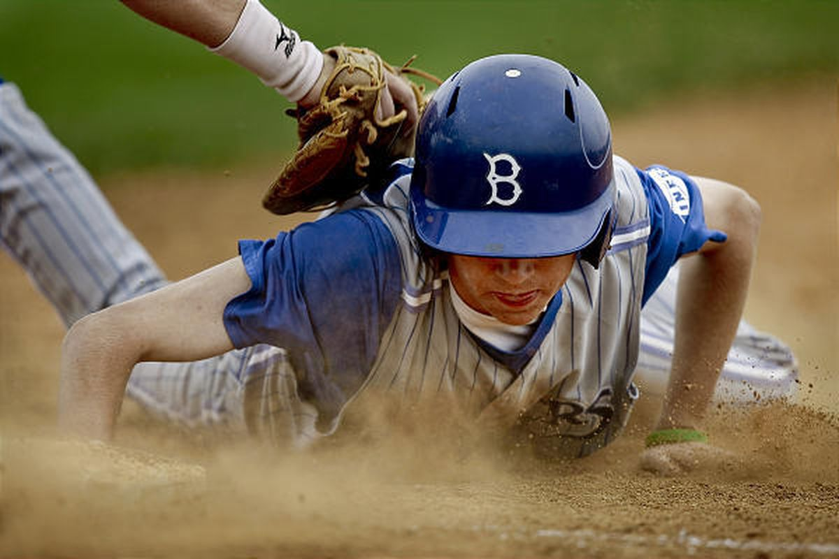 Bingham High School's TJ Bowcutt slides under the tag and back safely to first base during the Miners' dominating 11-0 victory on Tuesday over Taylorsville High.