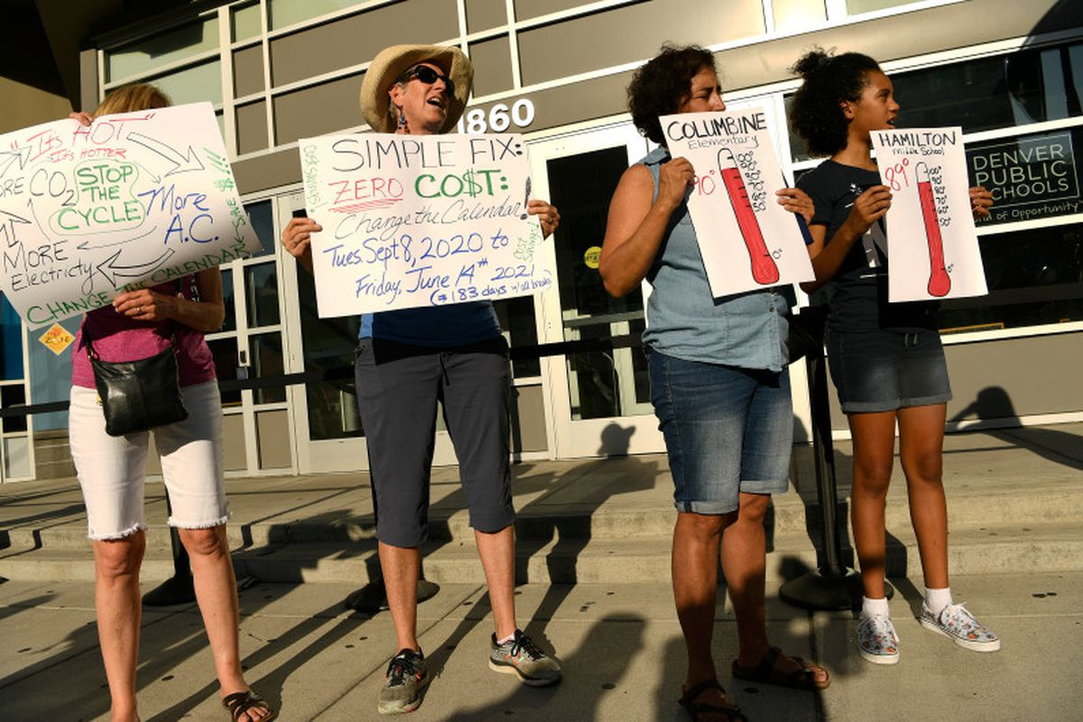 Margaret Bobb, second from left, a retired Denver teacher, holds a sign to protest hot classrooms in August 2019.