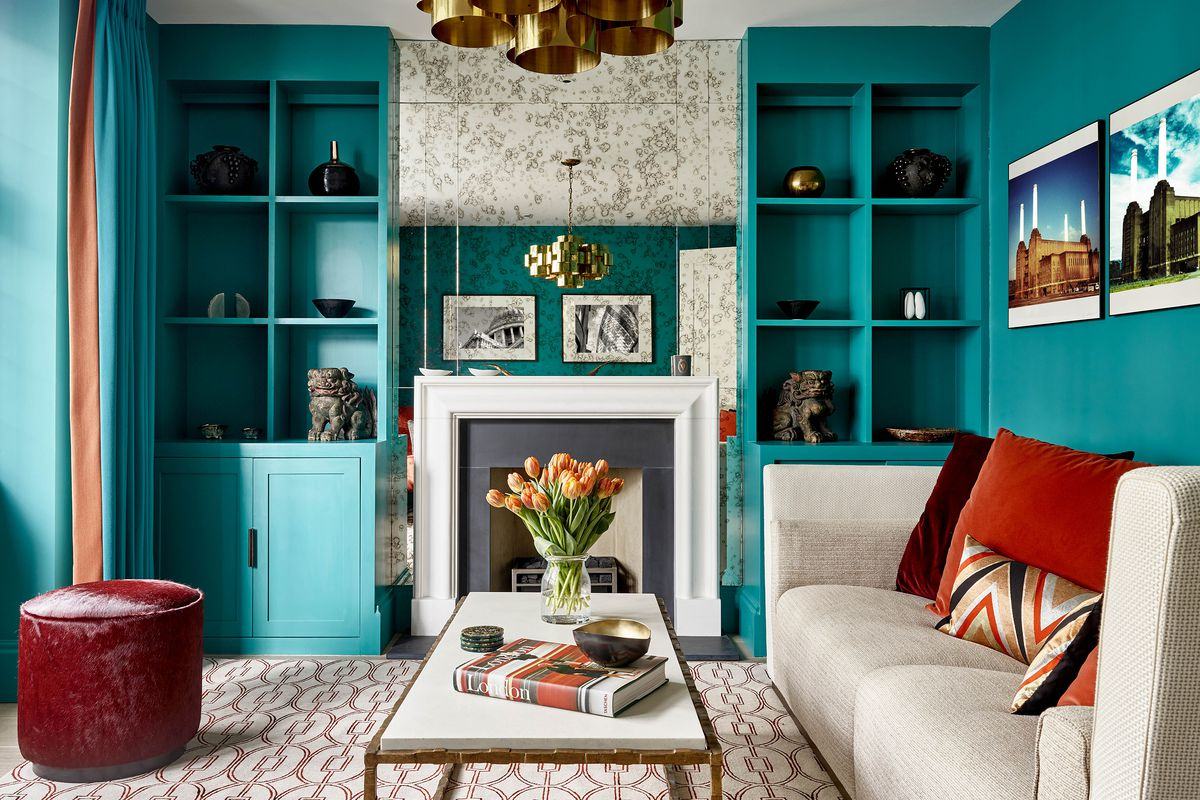Blue-green painted bookshelves and wall with red-orange accents.
