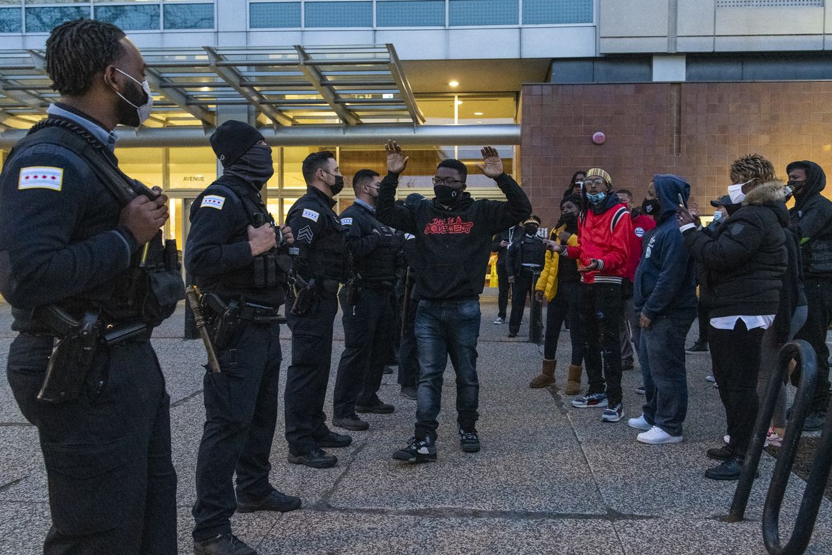 Community activist Ja'Mal Greene walks up and down a police line with his hands up outside Chicago Police Headquarters, during a protest in response to the release of the body camera footage that shows police killing Adam Toledo in late March, Thursday, April 15, 2021.   Tyler LaRiviere/Sun-Times