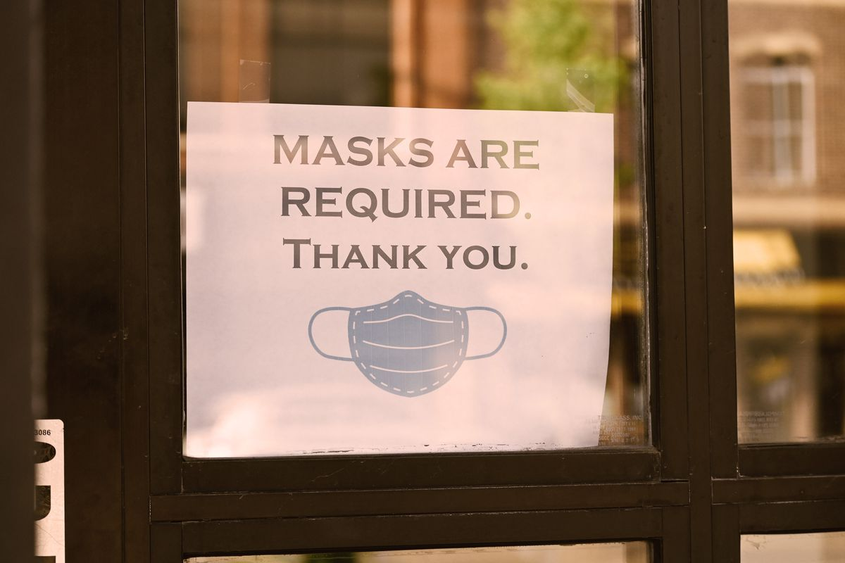 """Paper sign in a window reading """"Masks are required. Thank you."""" with an image of a disposable paper mask."""