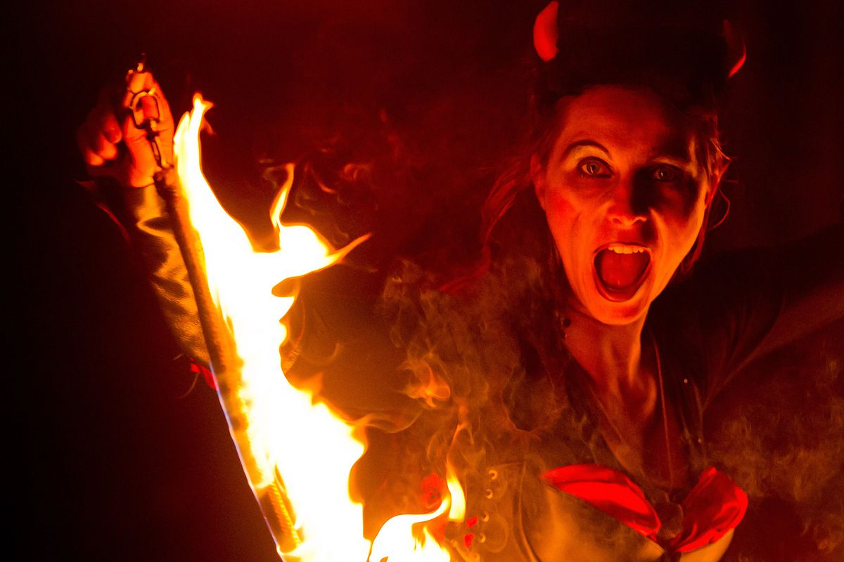A young woman dressed as a devil waves with fire in streets on December 5, 2013 in Hradec Kralove, Czech Republic.