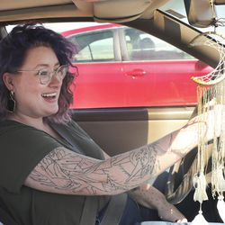 Taylor Voorhis waits in line with hundreds of motorists at the Division of Motor Vehicles drive-thru window in Draper on Friday, April 3, 2020.Some waited in line for hours.