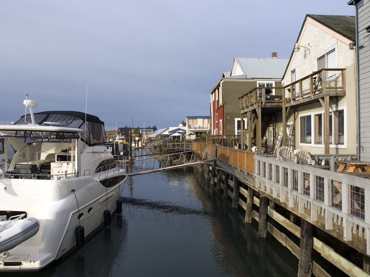 Short, older buildings with peaked roofs along a narrow boardwalk facing water. There's a large motorboat to the left.