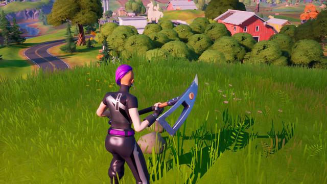A Fortnite player stands on top of a hill overlooking a farm