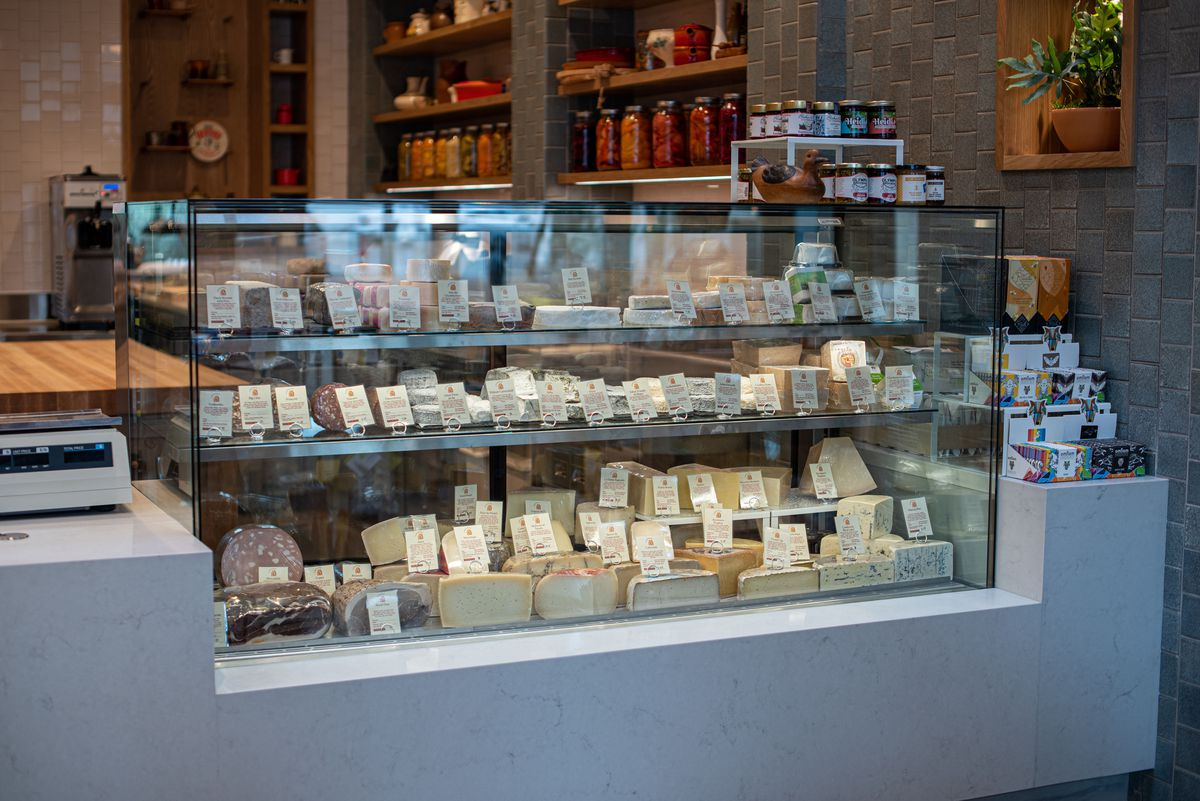 A glass case for cheeses of all sorts, complete with hand-written signs.