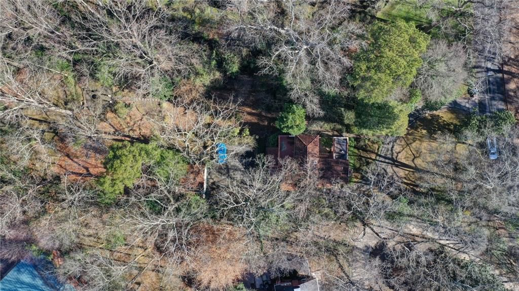 A drone image of a home's lot with many trees.