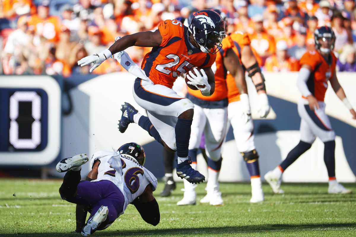 Melvin Gordon #25 of the Denver Broncos jumps over Geno Stone #26 of the Baltimore Ravens at Empower Field At Mile High on October 3, 2021 in Denver, Colorado.