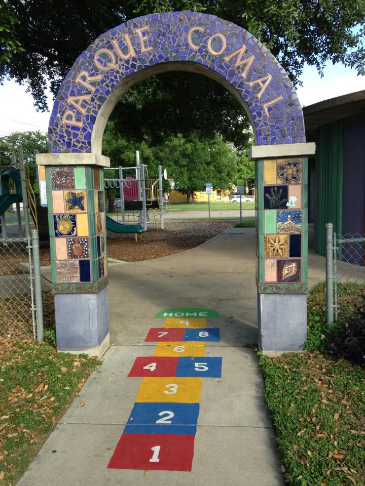 Purple mosaic arch that says Parque Comal with hopscotch grid on sidewalk and trees and playground behind