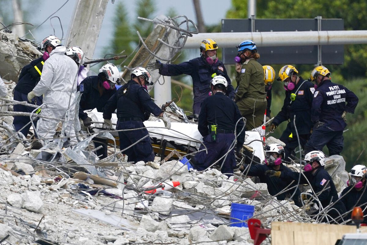 Rescue workers move a stretcher containing recovered remains at the site of the collapsed Champlain Towers South condo building, Monday, July 5, 2021 in Surfside, Fla.