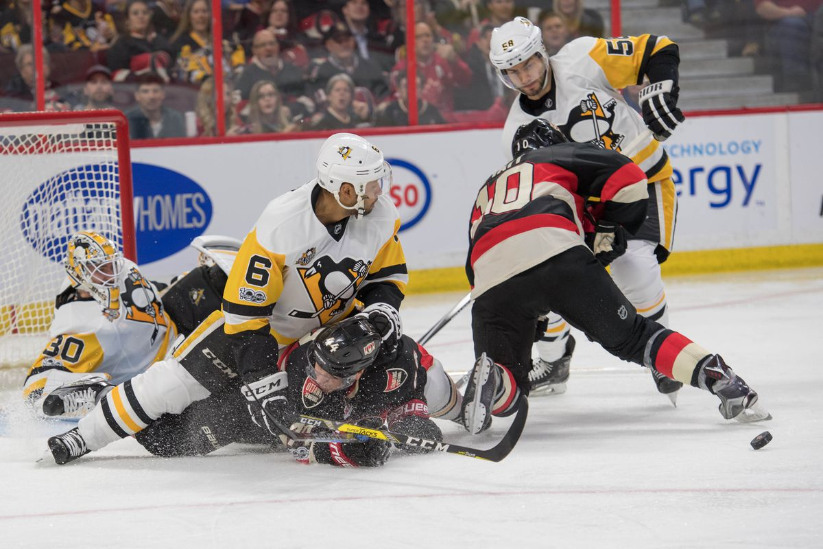 Fredrik Claesson of the Ottawa Senators intensely stares and defends  against Sidney Crosby of the Pittsburgh