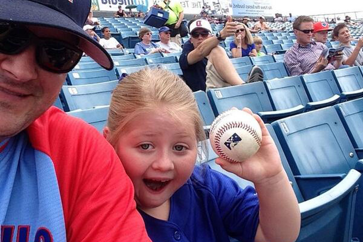 A Cubs fan proudly displays a ball given to her by Jonathan Mota in Nashville