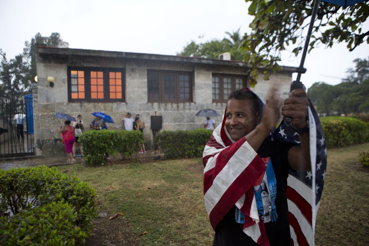 Cuban man clapping wrapped in American flag