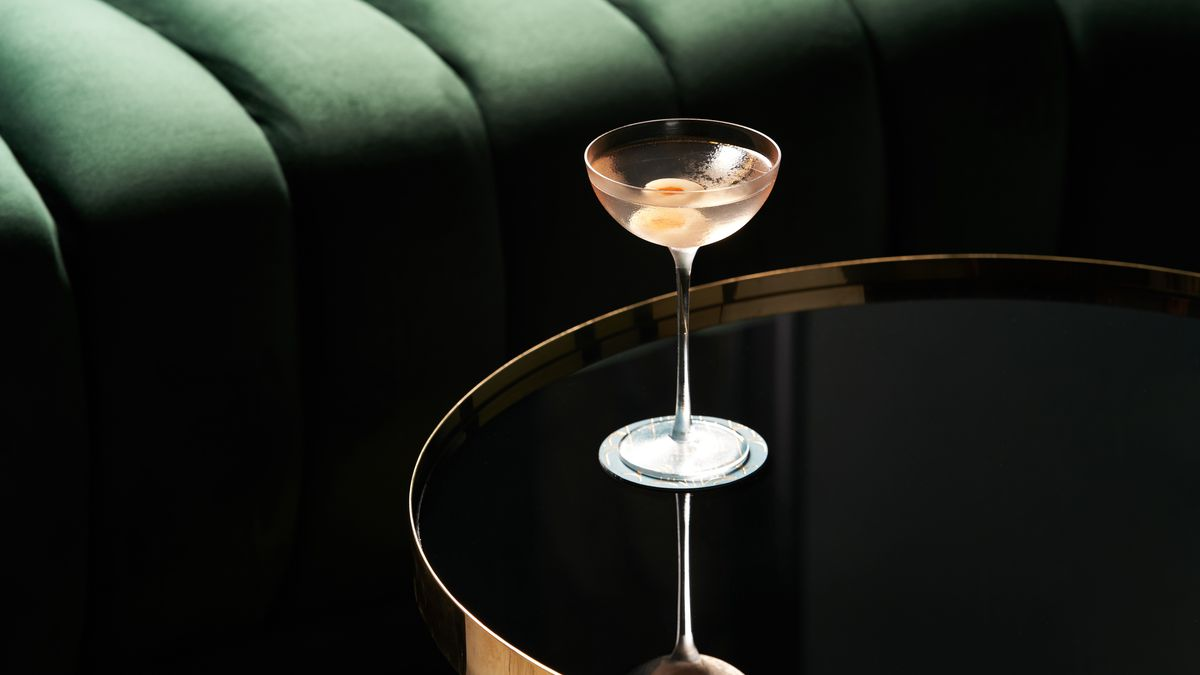 A lone martini sits on a glass table near a dark green booth draped in shadows