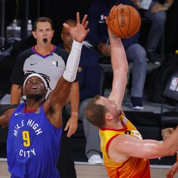 Joe Ingles #2 of the Utah Jazz grabs a rebound against Jerami Grant #9 of the Denver Nuggets in Game 4 of an NBA basketball first-round playoff series, Sunday, Aug. 23, 2020, in Lake Buena Vista, Fla.
