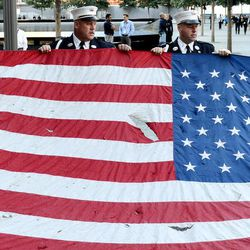 Police officers of the Port Authority of New York and New Jersey, carry an American flag that flew over at the World Trade Center towers, during the 11th anniversary ceremonies at the site of the World Trade Center, in New York, Tuesday Sept. 11, 2012.