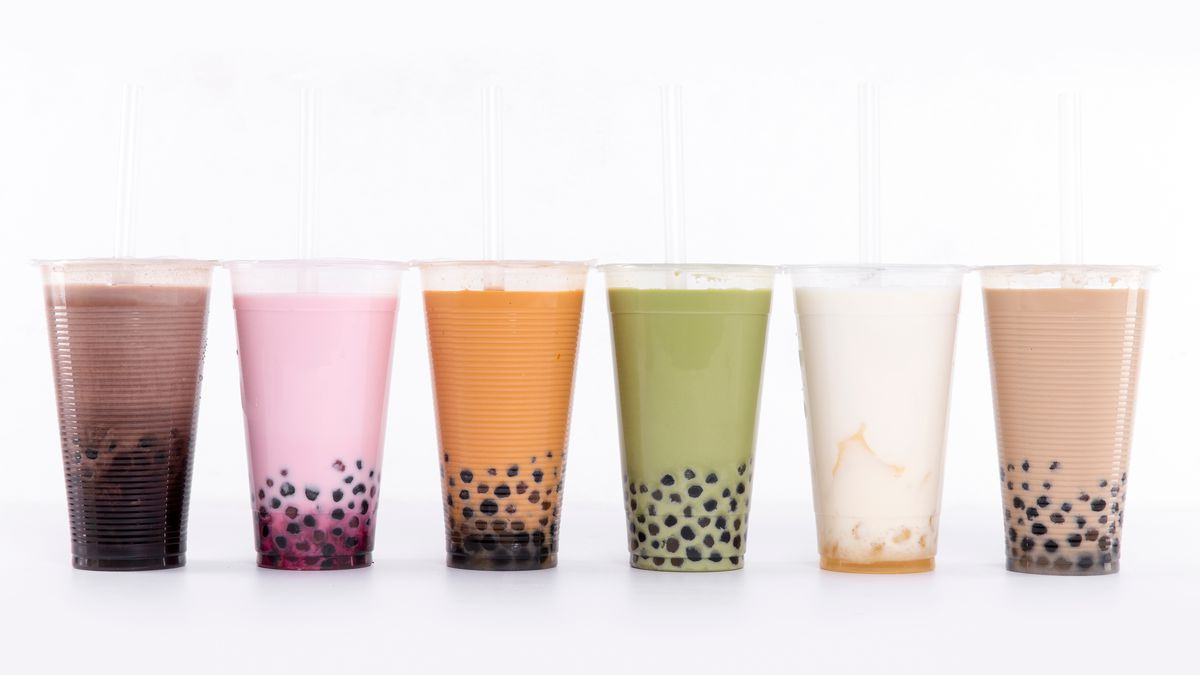 A row of six cups of different colors of bubble tea on a white background.
