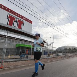 Casey Hill runs by Rice-Eccles Stadium while competing in the Deseret News Half Marathon in Salt Lake City on Friday, July 23, 2021.