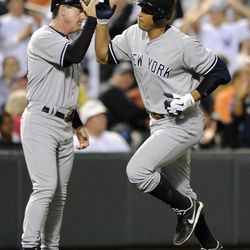 New York Yankees' Alex Rodriguez, right, is greeted by third base coach Rob Thomson, left, after he hit a home run against the Baltimore Orioles during the eighth inning of a baseball game, Saturday, Sept. 8, 2012, in Baltimore. The Orioles won 5-4.