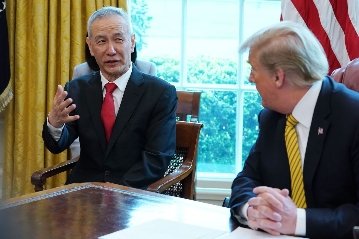 Chinese Vice Premier Liu He and President Donald Trump sit at a conference table in the White House.