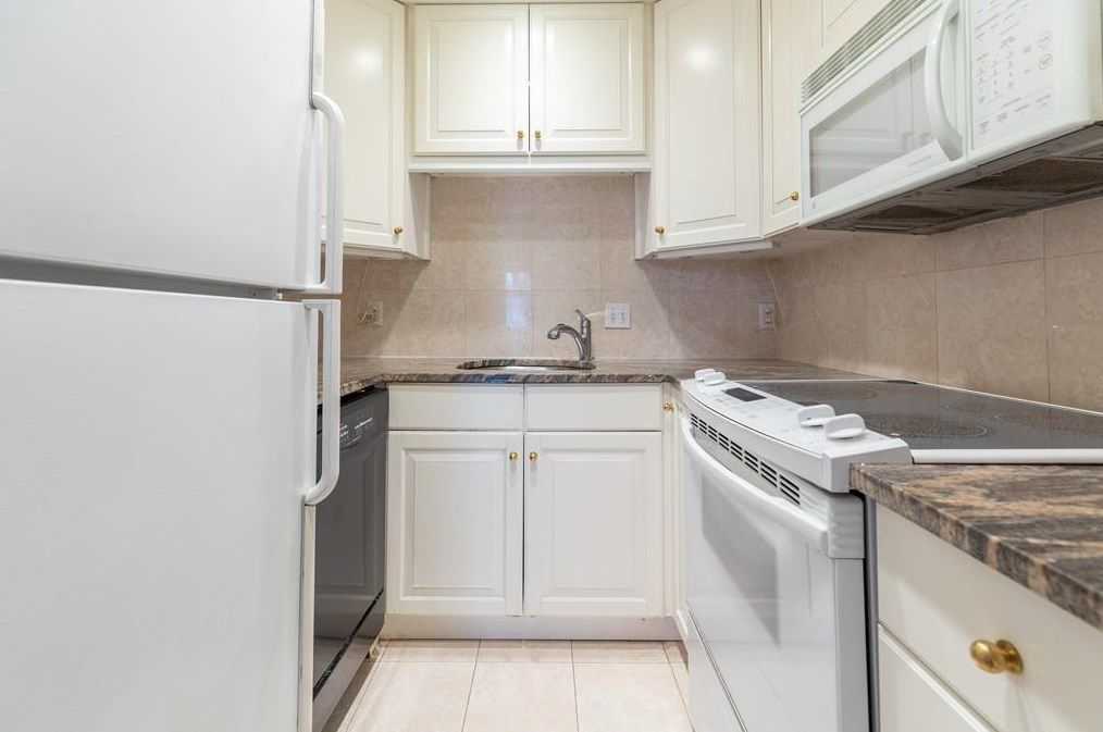 A kitchen with a U-shaped counter and a closeup of the fridge.