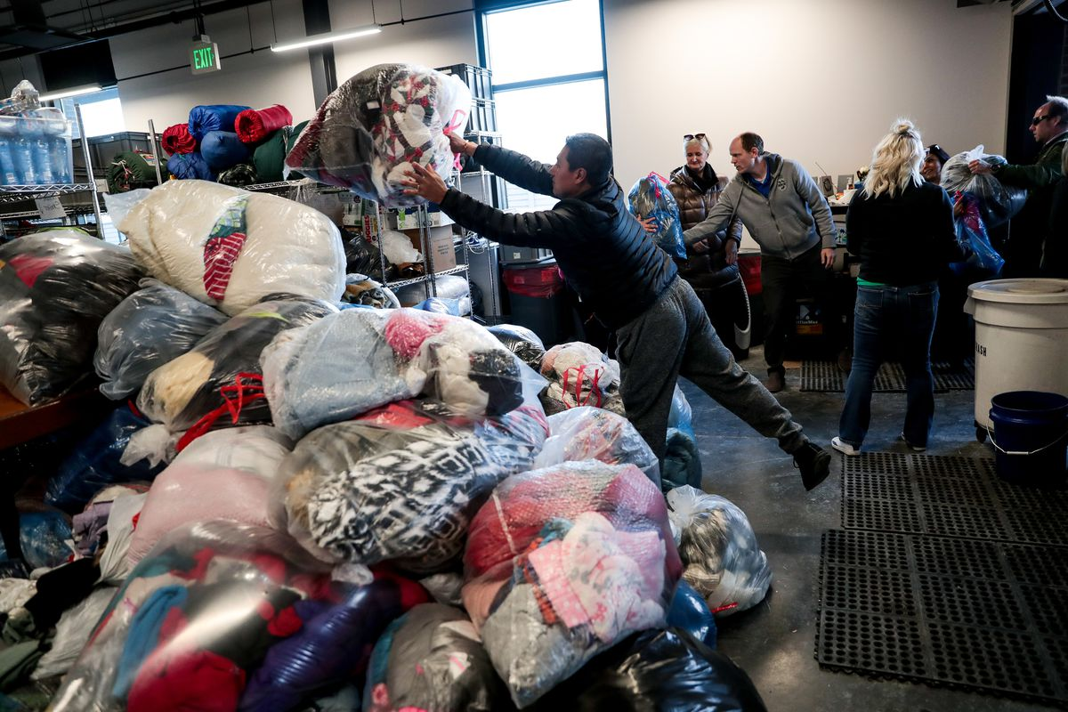 Roger Rodriguez, whose wife Luisa Rodriguez works at Check City, helps deliver coats collected during the company's Warm Hearts Coat Drive to the men's resource center in South Salt Lake on Tuesday, Dec. 3, 2019.