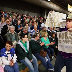 Monica Zoltanski carries signs during a town hall meeting at the Salt Lake County Equestrian Park in South Jordan, Monday, April 25, 2016.