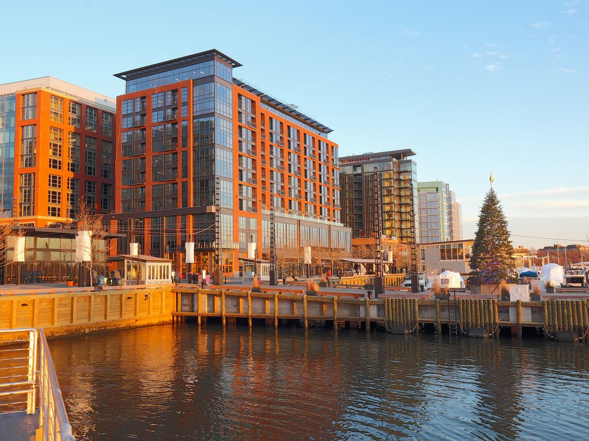 A waterfront development with modern mixed-use buildings. A holiday tree is seen on a pier.