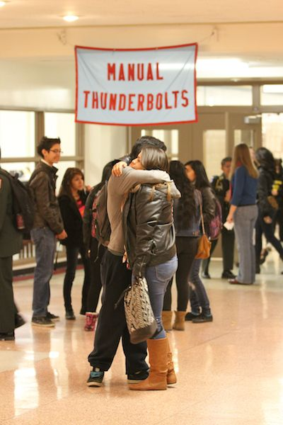Manual High School students embrace in the school's hall. The school's model invokes restorative justice.