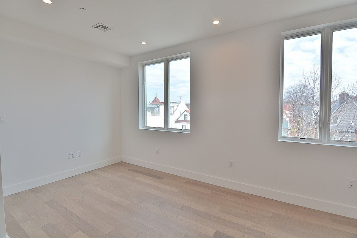 A living area with light hardwood floors and two windows.