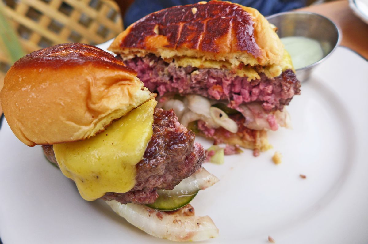 A whole burger cut in half with rare ground beer, chopped onions, and orange cheese seen.