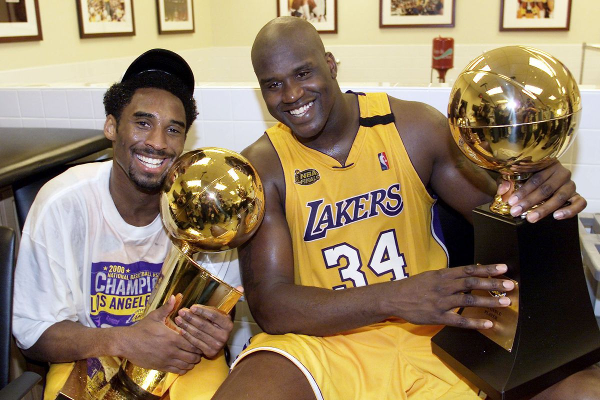 Kobe Bryant (L) of the Los Angeles Lakers holds th