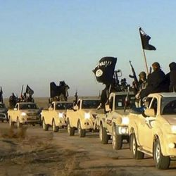 """FILE - In this undated file photo released by a militant website, which has been verified and is consistent with other AP reporting, militants of the Islamic State group hold up their weapons and wave flags on their vehicles, in a convoy on a road leading to Iraq, from Raqqa, Syria. A major battle to liberate the northern Syrian city of Raqqa from Islamic State militants is looming, with U.S. officials looking to build on momentum from the battlefields in Mosul. Armed with a new Pentagon plan to """"rapidly defeat"""" the militants in both countries, President Donald Trump is now mulling options for upping the fight, which a top U.S. commander says he expects to be concluded within six months. (Militant website via AP, File)"""